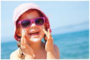 ребенок улыбается и крем на лице