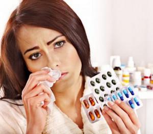 Девушка с насморком держит в руках разные таблетки