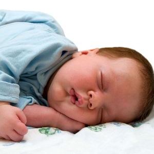 Малыш запрокидывает голову назад во сне