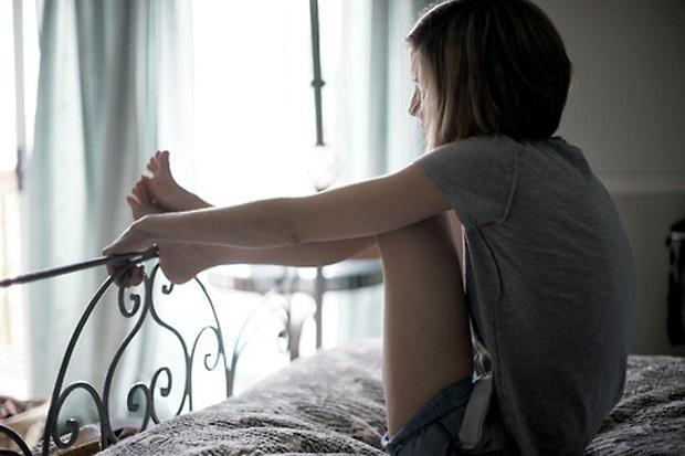 Грустная девушка на кровати
