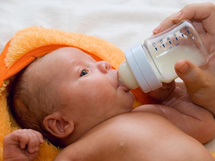 Малыша кормят смесью из бутылочки
