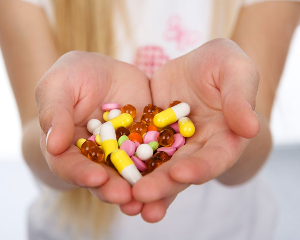 капсулы и таблетки в ладонях