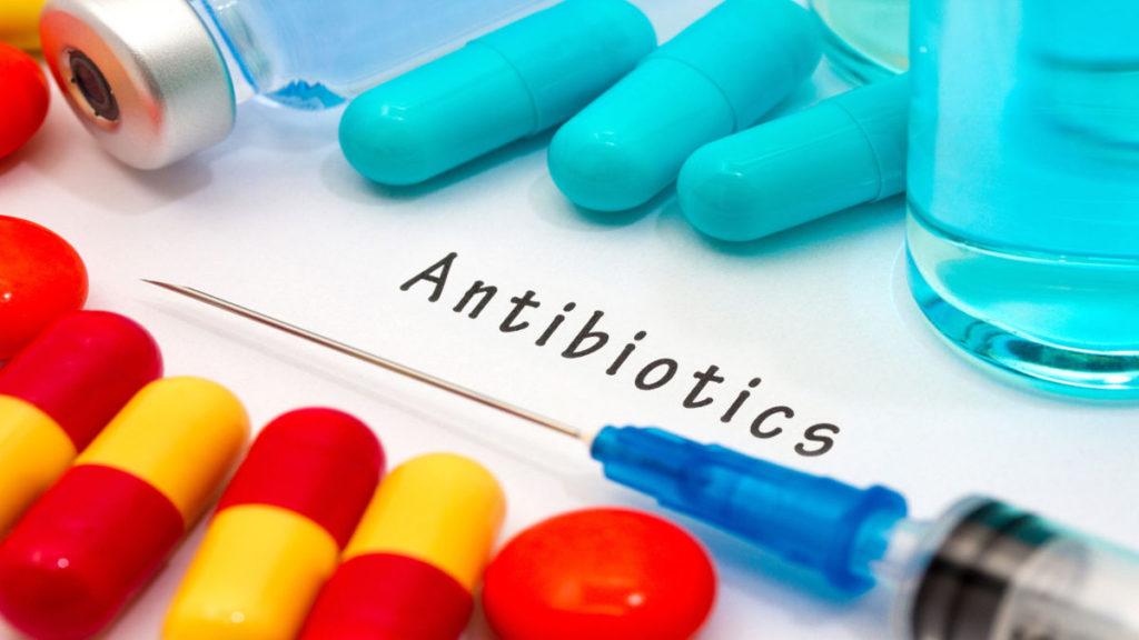 Слово антибиотики на белом листе бумаги, шприц, таблетки