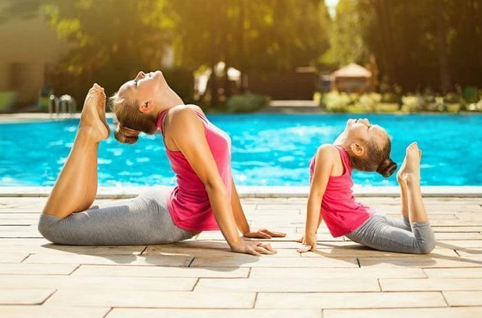 Мама с дочкой занимаются гимнастикой у бассейна