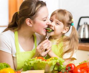 Мама и дочка едят овощи