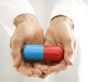 Красно-синяя таблетка в руках