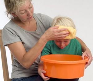 Ребенка тошнит над оранжевым тазиком