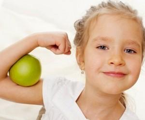 Здоровая и счастливая девочка сжала рукой зеленое яблоко