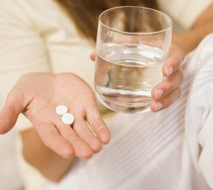 Две таблетки и стакан воды в руках у женщины