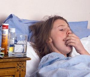 Больная девушка лежит под синим одеялом